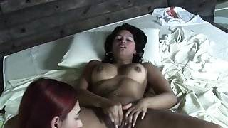 Two lesbos fist fucking on the bed fingering their pussies